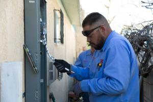 A TLC Electrician repairs a circuit box in a home in albuquerque