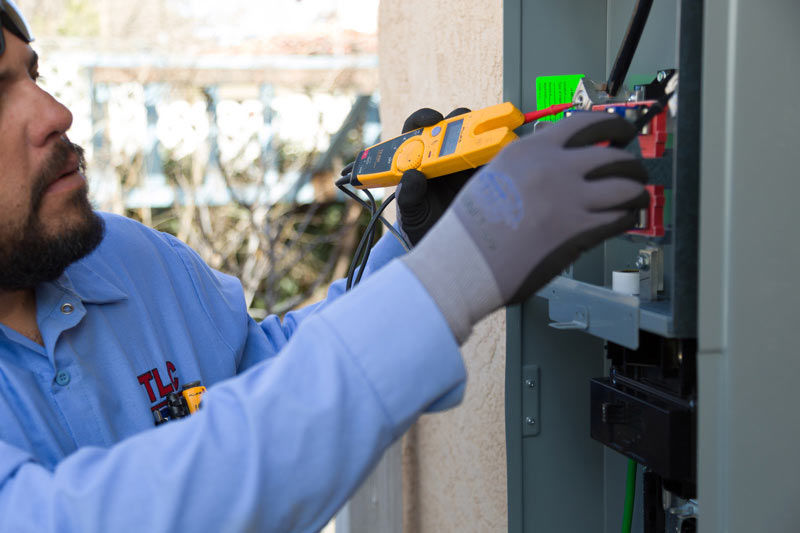 A TLC Plumbing Electrician repairs a circuit box.